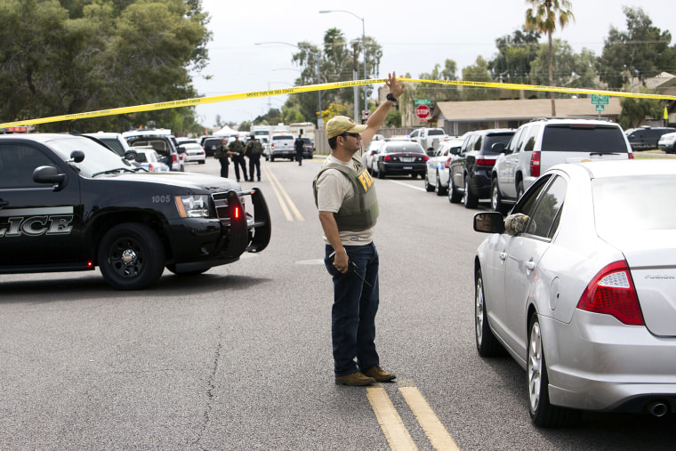 An FBI agent lifts police tape at one of the scenes of a multiple location shooting that has injured at least four people in Mesa, Arizona on March 18, 2015. (Photo by Deanna Dent/Reuters)