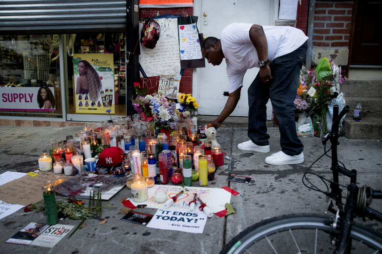 A mourner places a candle at a memorial for Eric Garner, a Staten Island man who died while being arrested by New York City police, on July 22, 2014, in New York. (Photo by John Minchillo/AP)
