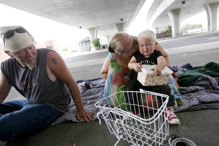 Tealla Dilka, with her husband Will at left, plays with her 18-month-old son David as they lay on the asphalt underneath the 16th Street bridge in Boise, Idaho on June 25, 2014.