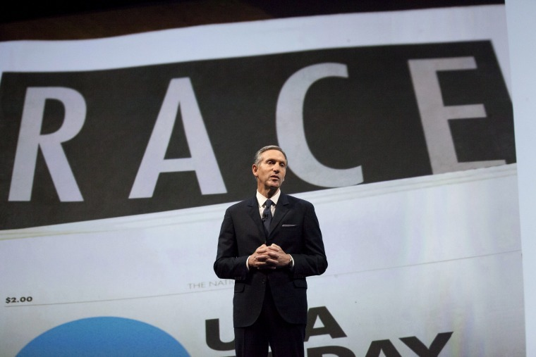 """Starbucks Corp Chief Executive Howard Schultz, pictured with images from the company's new """"Race Together"""" project behind him, speaks during the company's annual shareholder's meeting in Seattle, Washington March 18, 2015. (Photo by David Ryder/Reuters)"""