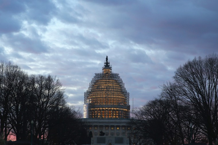 The early morning sun begins to rise behind the U.S. Capitol building on Jan. 20, 2015 in Washington, DC. (Photo by Mark Wilson/Getty)