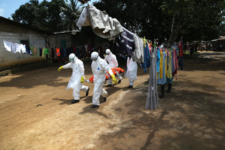 An Ebola burial team carries the body of a woman from a home in the New Kru Town suburb on Oct. 10, 2014 in Monrovia, Liberia. (Photo by John Moore/Getty)