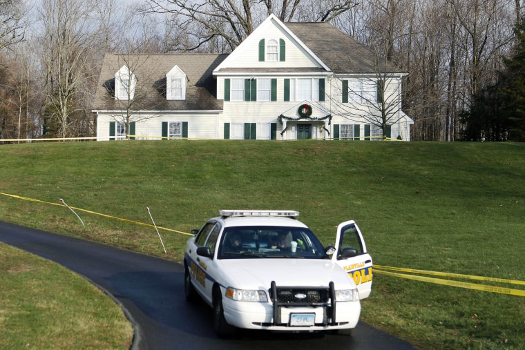 In this Dec. 18, 2012, file photo, a police cruiser sits in the driveway of the home of Nancy Lanza in Newtown, Conn., the Colonial-style house where she had lived with her son Adam Lanza. (Photo by Jason DeCrow/AP)