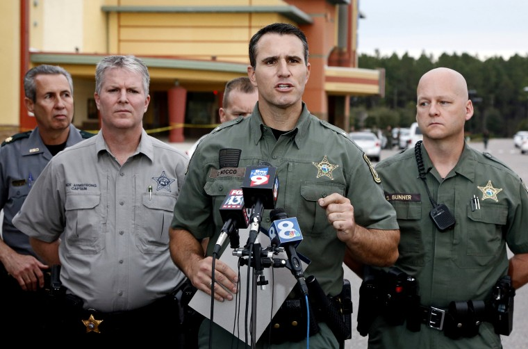 Pasco County Sheriff Chris Nocco (C) speaks to the media as police tape surrounds the Cobb Grove 16 movie theater, where a moviegoer shot and killed one person and wounded another, in Wesley Chapel, Fl., Jan. 13, 2014. (Photo by Mike Carlson/Reuters)