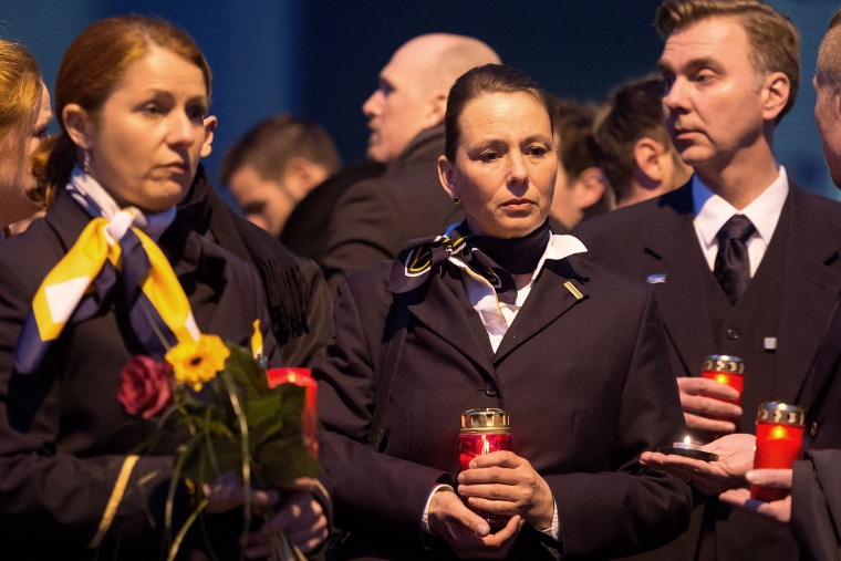 Staff members of Germanwings and Lufthansa stand in front of the headquarter of air carrier Germanwings placing flowers and candles at the main entrance in Cologne, Germany, March 24, 2015. (Photo by Marius Becker/picture-alliance/dpa/AP)
