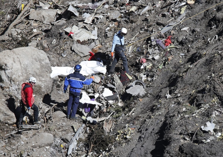 Search and rescue workers make their way through debris at the crash site of the Germanwings Airbus A320 that crashed in the French Alps, above the town of Seyne-les-Alpes, southeastern France on March 26, 2015.