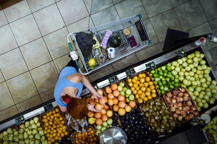 A grocery shopper picks through fruit in the produce section. Most fruits and vegetables are culled due to aesthetic issues rather than safety concerns.