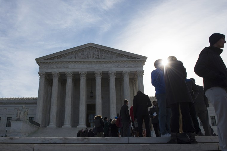People wait in line outside the Supreme Court in Washington on March 23, 2015.