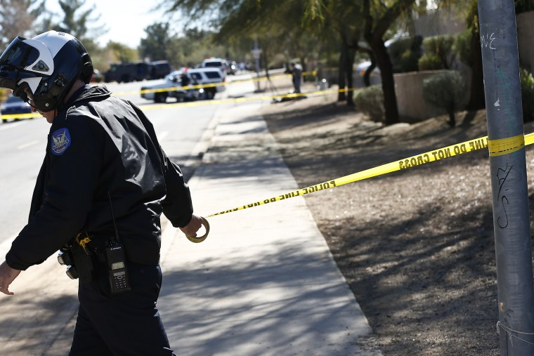A Phoenix Police Department officer puts up police tape near a crime scene on Jan. 30, 2013. (Photo by Ross Franklin/AP)