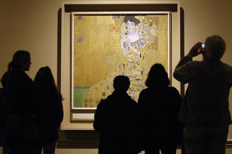 Museum visitors study 1907 painting by Austrian artist Gustav Klimt in Los Angeles