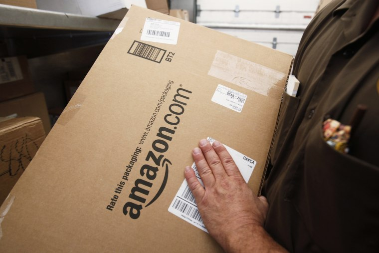 In this Oct. 18, 2010 file photo, United Parcel Service (UPS) driver delivers an Amazon box. (Photo by Paul Sakuma/AP)