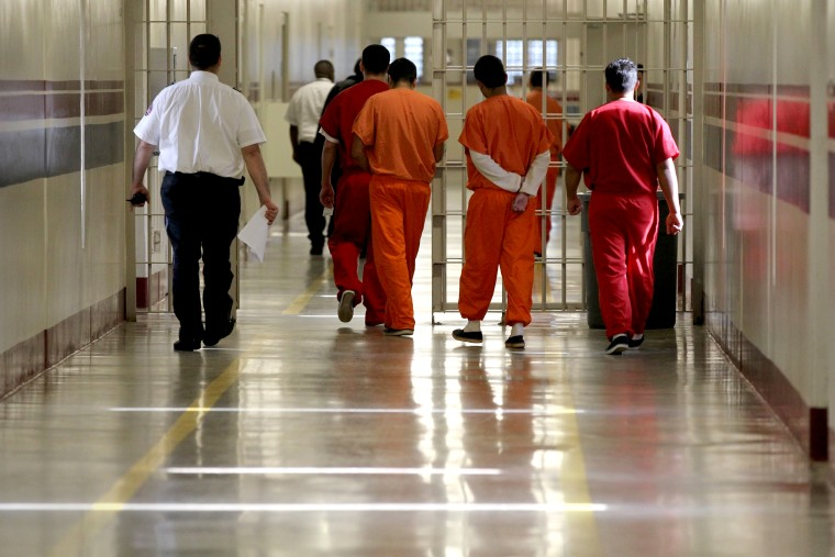 Detainees at the Stewart Detention Center in Lumpkin, Ga. are escorted through a corridor. (Photo by Jonathan Wiggs/The Boston Globe via Getty)