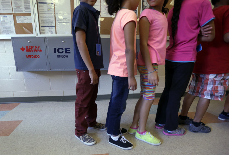 Detained immigrant children line up in the cafeteria at the Karnes County Residential Center, a temporary home for immigrant women and children detained at the border, Sept. 10, 2014, in Karnes City, Texas. (Photo by Eric Gay/AP)