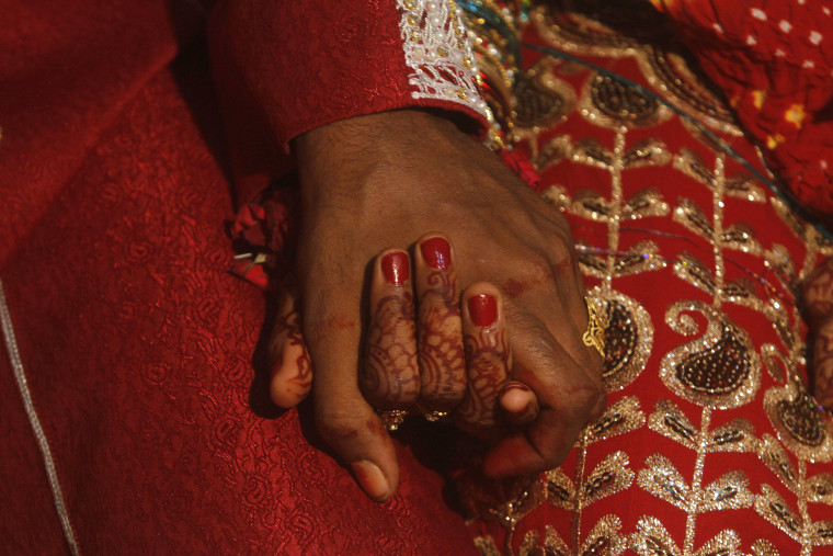 A bride and groom hold hands as they sit together during a mass marriage ceremony held in Karachi, Nov. 30, 2013. (Photo by Athar Hussain/Reuters)