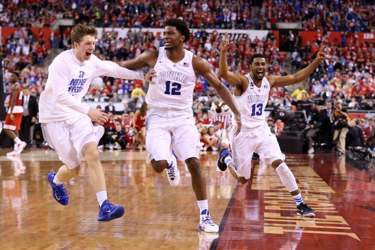 Justise Winslow #12 and Matt Jones #13 of the Duke Blue Devils celebrate with teammates after defeating the Wisconsin Badgers during the NCAA Men's Final Four National Championship on April 6, 2015 in Indianapolis, Ind. (Photo by Andy Lyons/Getty)