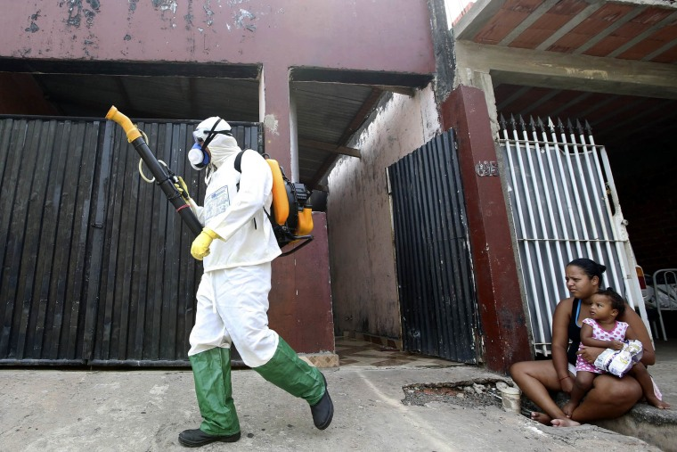A national health official walks past residents as he carries out fumigation to help control the spread of dengue fever, which are caused by viruses carried by mosquitoes, in Rio Claro, Sao Paulo on March 6, 2015.