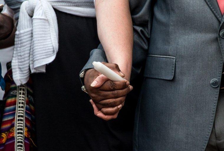 Two people hold hands during a candlelight vigil for Walter Scott in North Charleston, SC on April 10, 2015. (Photo by Ron Harris/AP)