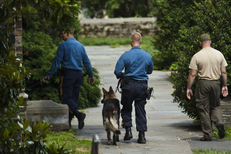 New Jersey police officers patrol on foot with dogs inside the campus of Princeton University in New Jersey June 11, 2013. (Photo by Eduardo Munoz/Reuters)
