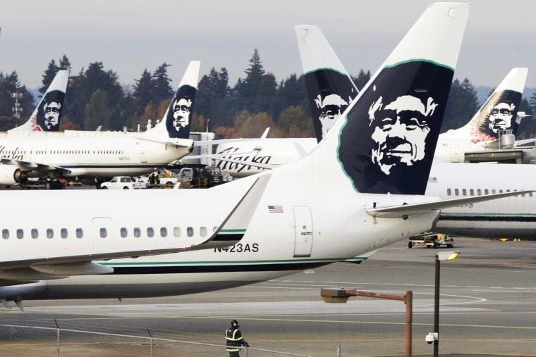 A ground crew member walks near Alaska Airlines planes parked at Seattle-Tacoma International Airport in SeaTac, Wash., Oct., 30, 2013. (Photo by Jason Redmond/Reuters)