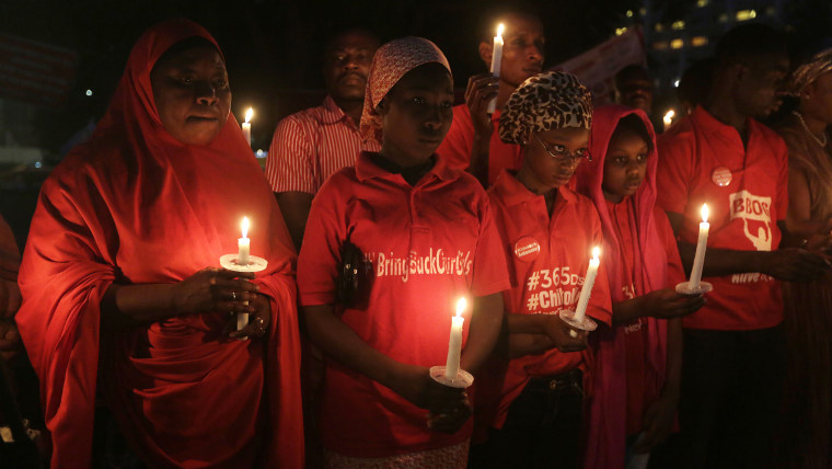 People hold candles during a vigil to mark the one year anniversary of the abduction of girls studying at the Chibok government secondary school, Abuja, Nigeria, April 14, 2015. (Photo by Sunday Alamba/AP)