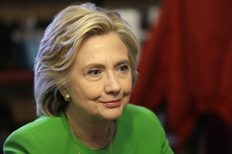 In this April 14, 2015, photo, Democratic presidential candidate Hillary Rodham Clinton meets with local residents at the Jones St. Java House in LeClaire, Iowa. (Photo by Charlie Neibergall/AP)
