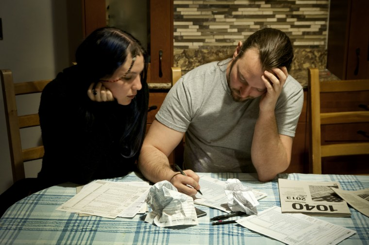 A couple does their taxes, April 13, 2014. (Photo by Patrick Colvin/Getty)