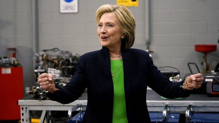 Former US Secretary of State Hillary Clinton pumps her fists in an auto shop as she campaigns for the 2016 Democratic presidential nomination at Kirkwood Community College in Monticello, Ia., April 14, 2015. (Photo by Rick Wilking/Reuters)