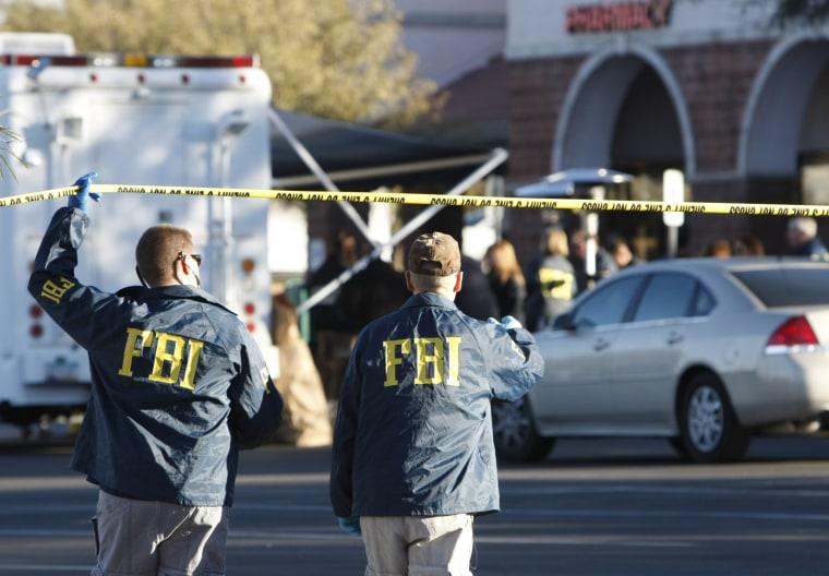 FBI agents process a shooting scene in Tucson, Ariz., Jan. 11, 2011. (Photo by Rick Wilking/Reuters)