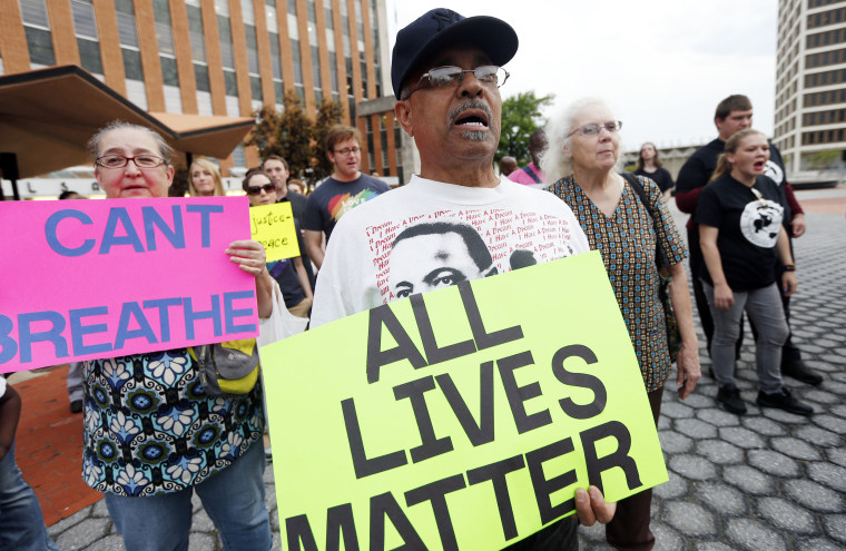 Albert Davis (right) and Susan Penn (left), both of Tulsa, hold signs as hundreds gather near Fourth Street and Denver Avenue, in hopes of having two Tulsa County Sheriff's deputies fired for their roles in the death of Eric Harris, on April 17, 2015