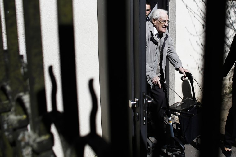 Former SS guard Oskar Groening, center, leaves the court building after the first day of the trial against him in Lueneburg, northern Germany, on April 21, 2015.