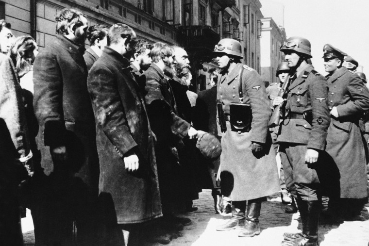 Nazi officers talk with citizens of the Warsaw ghetto, Poland, spring 1943. (Photo by AP)