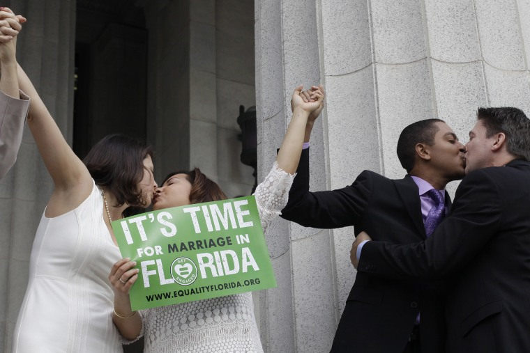 From right to left; Jeff Delmay, Todd Delmay, Karla Arguello and Catherina Pareto kiss after the same-sex couples were married in Miami, Fla. on Jan. 5, 2015. (Photo by Javier Galeano/Reuters)