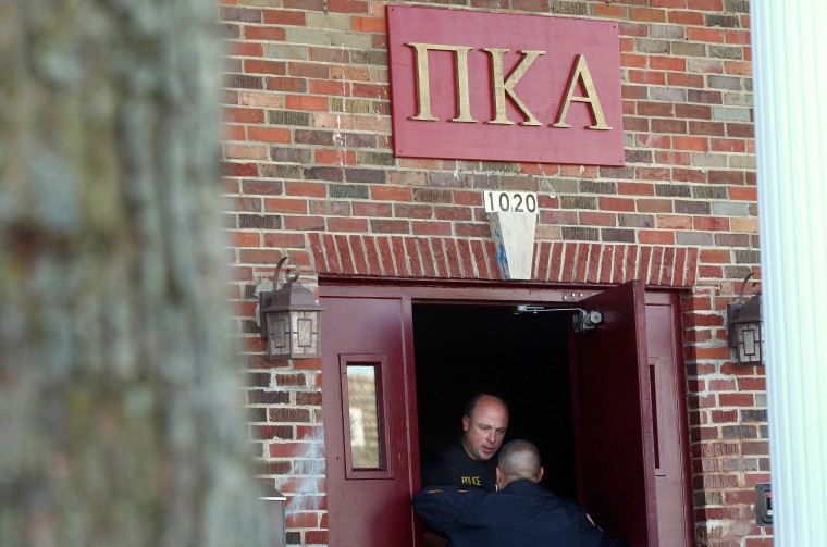 DeKalb and Northern Illinois University police speak in the doorway of the Pi Kappa Alpha house in DeKalb, Ill. where police were investigating the death of NIU freshman David Bogenberger, Nov. 2, 2012. (Photo by Kyle Bursaw/Daily Chronicle/AP)