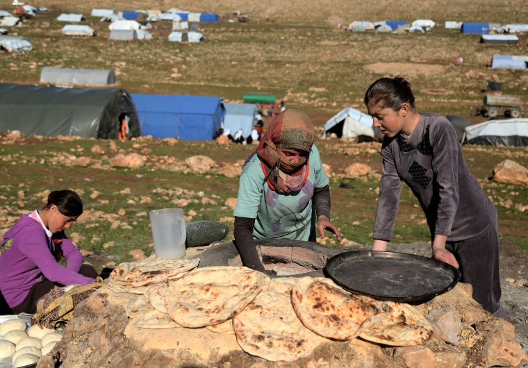 Yezidi women bake bread on the outskirts of Sinjar mountain, Mosul, March 2, 2015, after fleeing from ISIS attacks to a shelter in the Sinjar Mountain. (Photo by Emrah Yorulmaz/Anadolu Agency/Getty)
