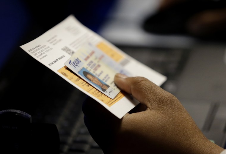 An election official checks a voter's photo identification at an early voting polling site in Austin, Texas, Feb. 26, 2014. (Photo by Eric Gay/AP)