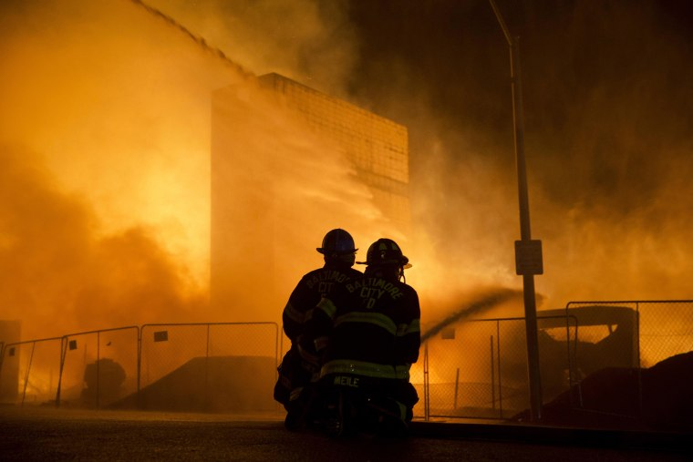 Firefighters battle a blaze on April 27, 2015, after rioters plunged part of Baltimore into chaos, torching a pharmacy, setting police cars ablaze and...