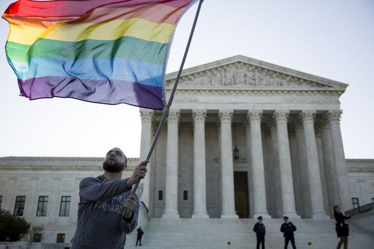 Same-sex marriage supporter Vin Testa, of Washington, DC, waves a rainbow pride flag near the Supreme Court, April 28, 2015 in Washington, DC.