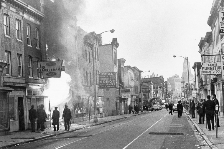 Fire shoots out from a Baltimore store on Gay Street as looting erupted in a five-block business section in Baltimore on April 6, 1968.