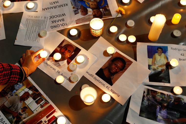A woman places a candle on top of pictures of the prisoners to be executed in Indonesia, during a vigil at Martin Place on April 28, 2015 in Sydney, Australia. (Photo by Daniel Munoz/Getty)