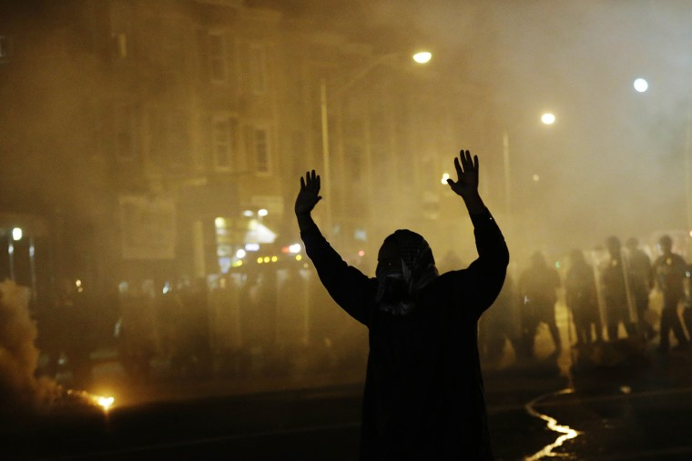 A protestor walks away as police in riot gear advance on the crowd after a 10 p.m. curfew went into effect in the wake of Monday's riots following the funeral for Freddie Gray, April 28, 2015, in Baltimore. (Photo by David Goldman/AP)