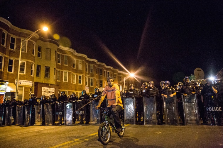 A protester sits in front of riot police minutes before a mandatory, city-wide curfew of 10 p.m. near the CVS pharmacy that was set on fire yesterday during rioting after the funeral of Freddie Gray, on April 28, 2015 in Baltimore, Md.