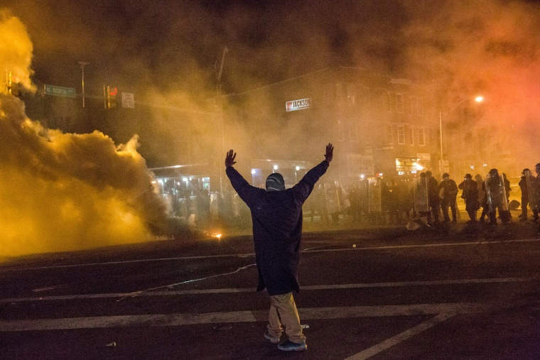 A protester walks through smoke as police enforce a mandatory, city-wide curfew of 10PM near the CVS pharmacy that was set on fire yesterday during rioting after the funeral of Freddie Gray, on April 28, 2015 in Baltimore, Md.