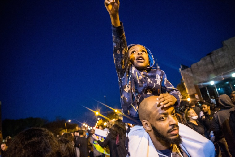 Protesters hang out front of riot police minutes before a mandatory, city-wide curfew of 10 p.m. near the CVS pharmacy that was set on fire yesterday during rioting after the funeral of Freddie Gray, on April 28, 2015 in Baltimore, Md.