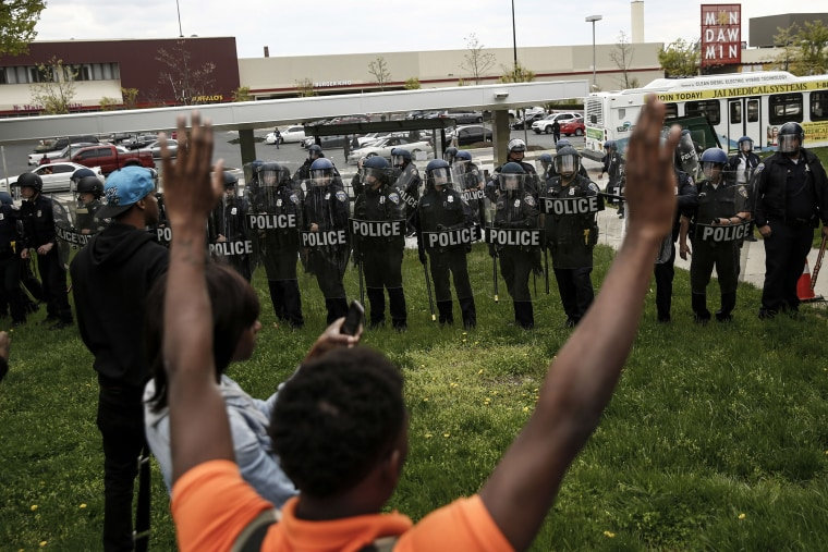 A protestors confronts Baltimore Police officers with his hands up near Mondawmin Mall on April 27, 2015 in Baltimore, Md.