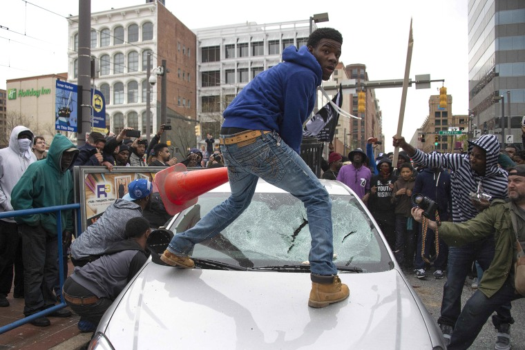 Demonstrators destroy the windshield of a Baltimore Police car as they protest the death Freddie Gray, an African American man who died of spinal cord injuries in police custody, in Baltimore, Md., April 25, 2015. (Photo by Jim Watson/AFP/Getty)