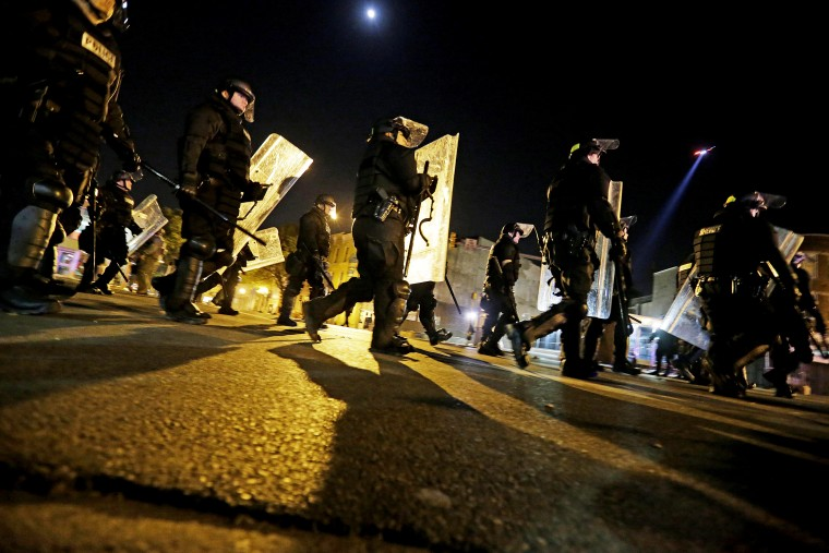 Police in riot gear return to a staging area after lining up to enforce a curfew imposed in the aftermath of rioting following Monday's funeral for Freddie Gray, who died in police custody, May 1, 2015, in Baltimore. (Photo by David Goldman/AP)