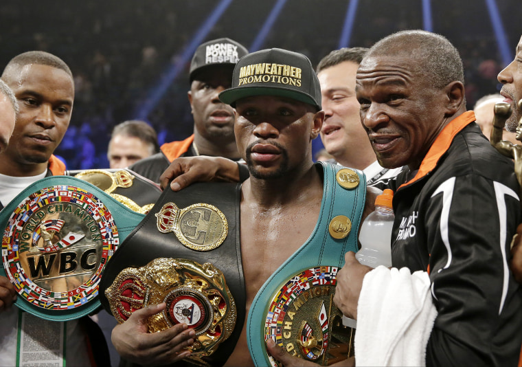 Floyd Mayweather Jr. poses with his champion's belts and his father, head trainer Floyd Mayweather Sr., after his victory over Manny Pacquiao, from the Philippines, in their welterweight title fight on May 2, 2015 in Las Vegas. (Photo by Isaac Brekken/AP)