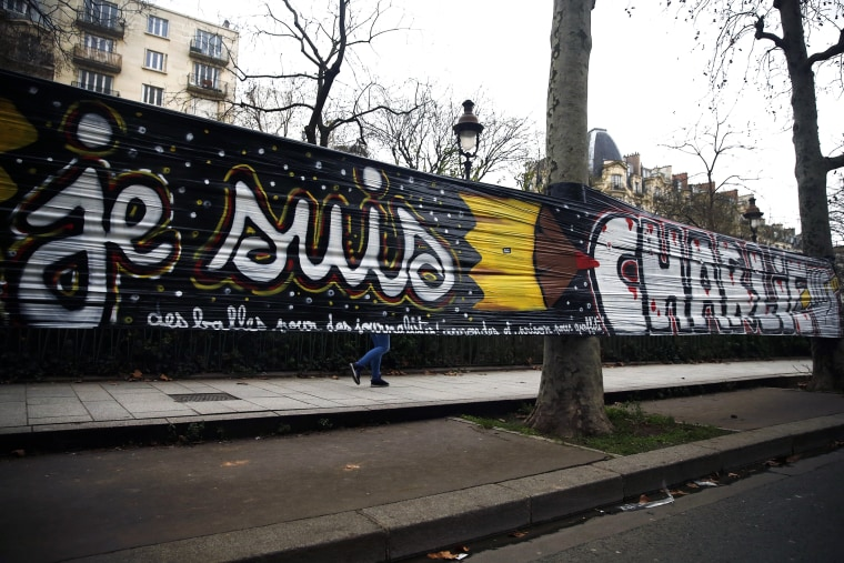 A woman walks behind a large banner stating 'Je suis Charlie' that is hung between trees next the 'Charlie Hebdo' offices in Paris, France, on Jan. 12, 2015. (Photo by Etienne Laurent/EPA)