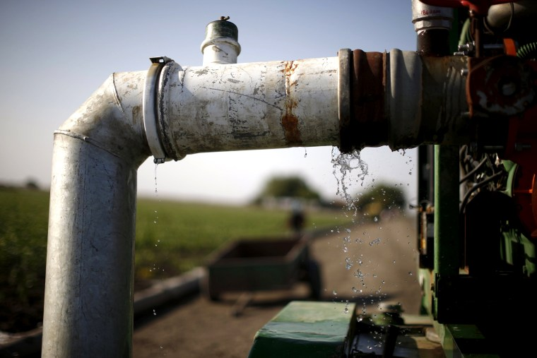 An irrigation pipe leaks in Los Banos, Calif. on May 5, 2015. (Photo by Lucy Nicholson/Reuters)