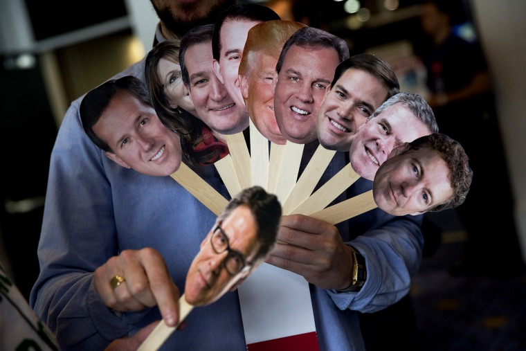 Adam Gabbatt of The Guardian newspaper holds images of possible Republican candidates during the Conservative Political Action Conference (CPAC) in National Harbor, Md. on Feb. 26, 2015.